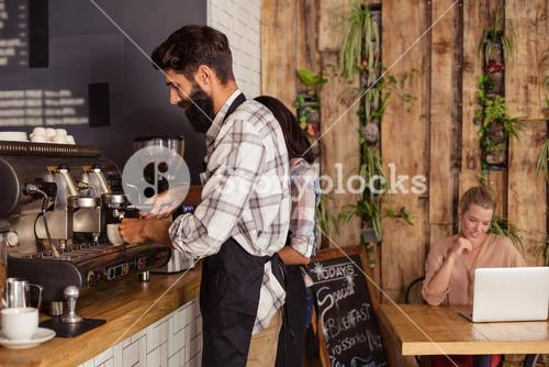 Waiters using a coffee machine and customer on a laptop