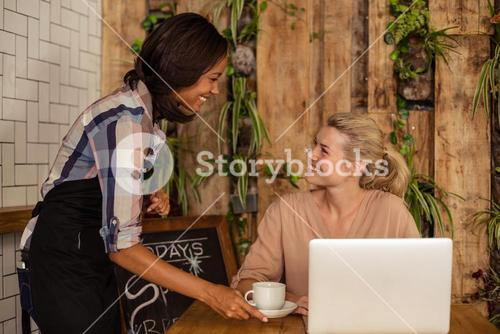 Waitress serving a coffee to a customer