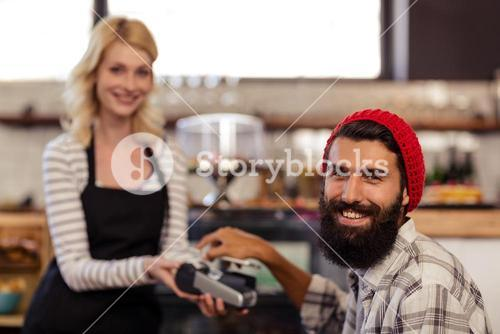 Customer paying by bank card reader with his smartphone
