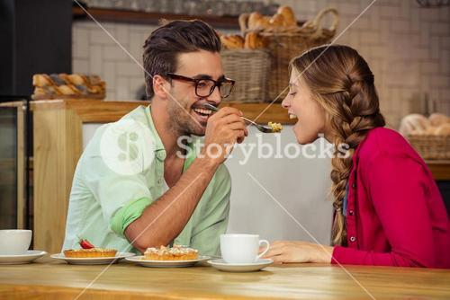 Smiling couple eating cake