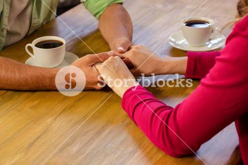 Couple holding hands in cafeteria