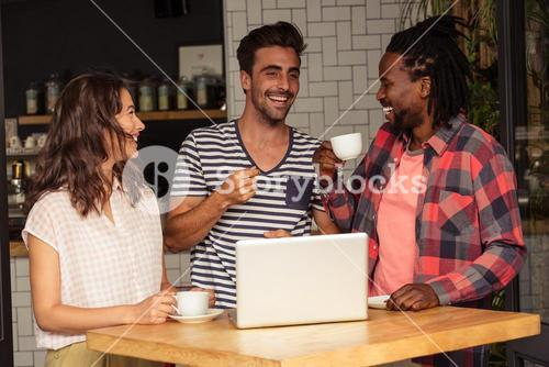 Friends interacting and laptop on the table