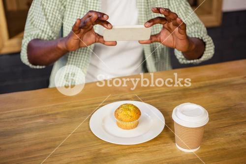 Man taking picture of a muffin