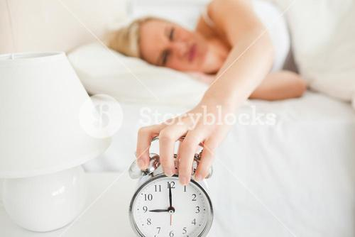 Upset woman switching off her alarm clock