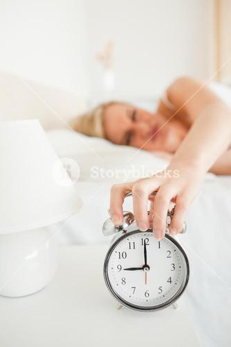 Portrait of a woman switching off her alarm clock