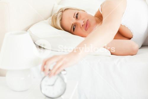 Upset blonde woman waking up