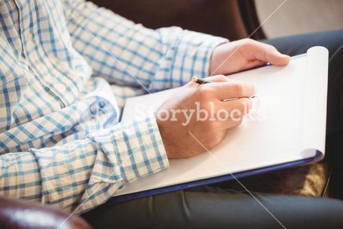 Business man writing on his clipboard