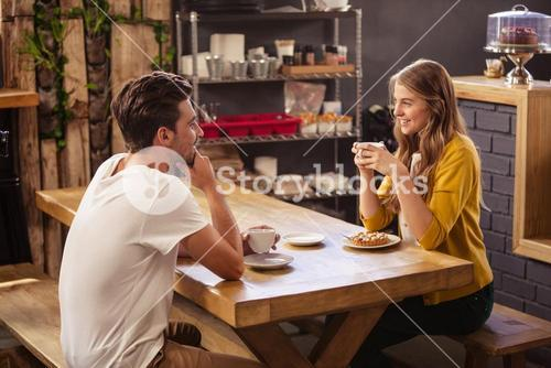 Two smiling hipsters drinking coffee