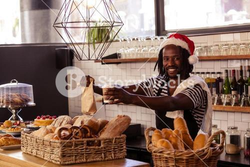 Smiling hipster employee serving take away products