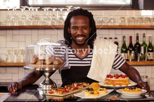 Portrait of hipster employee posing with pastries