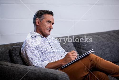 Businessman reflecting with his notepad