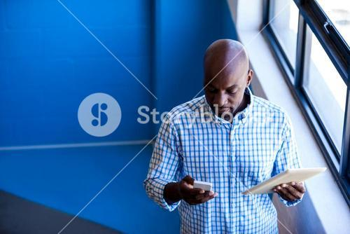 Casual businessman holding a mobile phone and tablet computer