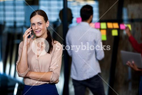 Focus on foreground of businesswoman calling
