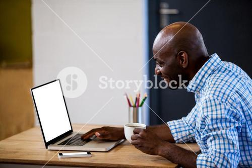 Profile view of businessman holding a coffee and typing on his laptop