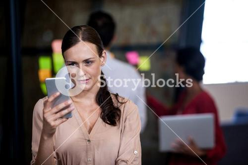 Focus on foreground of woman looking her mobile phone