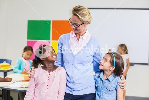 Smiling teacher and kids standing together with arm around