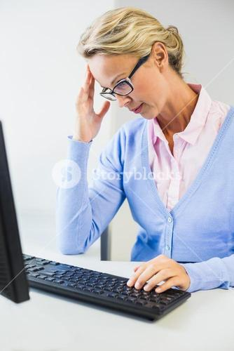 Teacher working on computer in classroom