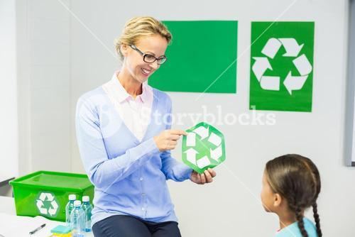 Teacher showing recycle logo to schoolgirl