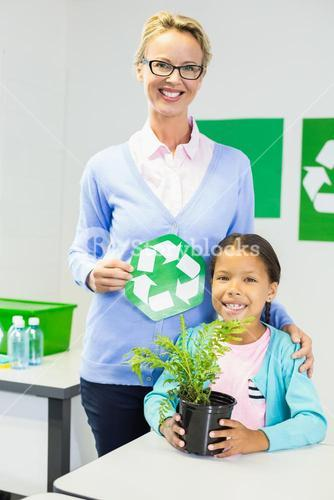 Teacher and schoolgirl with recycle logo in classroom