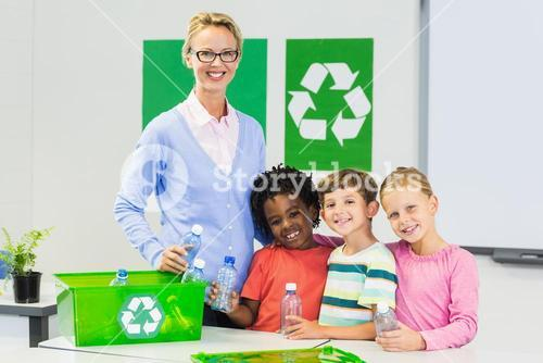 Portrait of teacher and kids standing in classroom