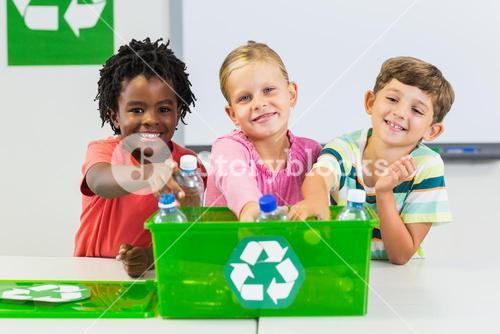 Kids holding recycled bottle in classroom
