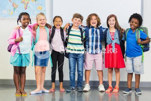 Smiling kids standing with arm around in classroom