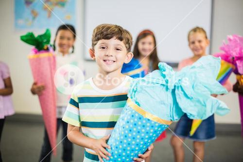 Schoolboy holding gift in classroom