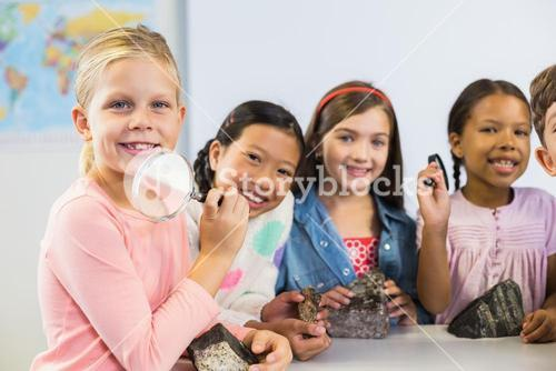 Portrait of kids holding magnifying glass in classroom