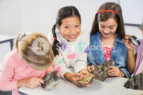Group of kids looking at specimen stone through magnifying glass