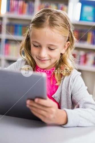Schoolgirl using digital tablet in library