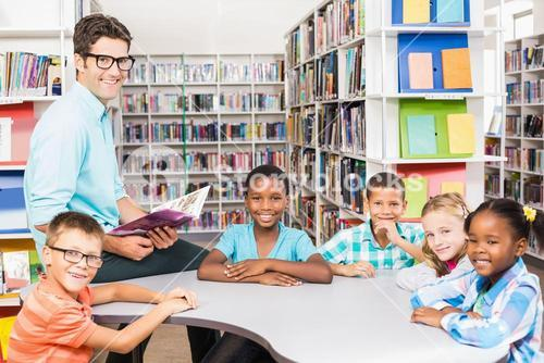 Portrait of teacher and kids in library