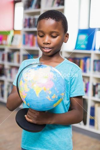 Schoolboy studying globe in library