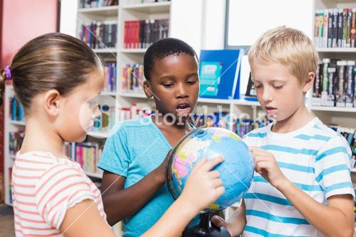 Kids studying globe in library
