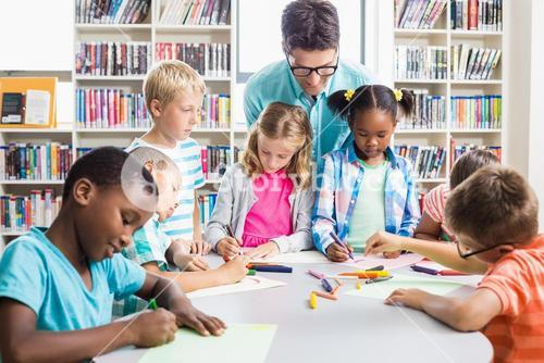 Teacher helping kids with their homework in library