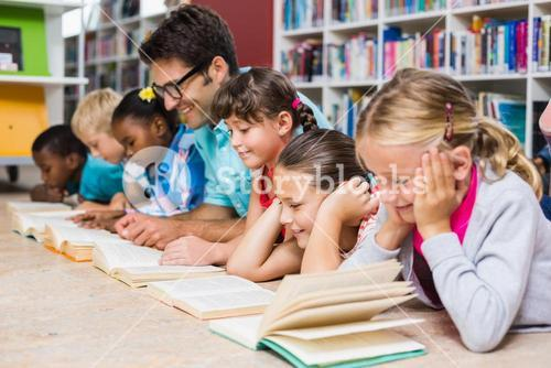 Teacher and kids reading book in library