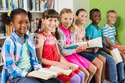 Portrait of kids reading book in library