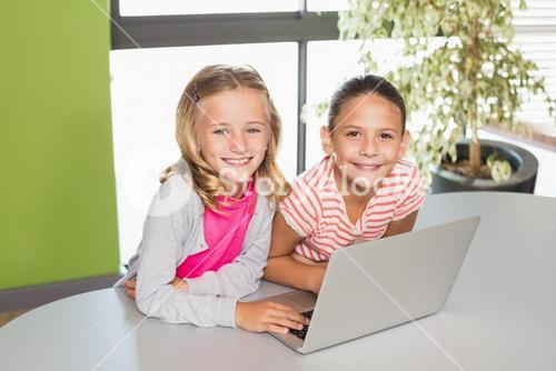 Kids using laptop in library