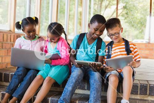 Kids sitting on staircase using laptop and digital tablet
