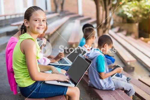 Kids sitting on bench and using laptop