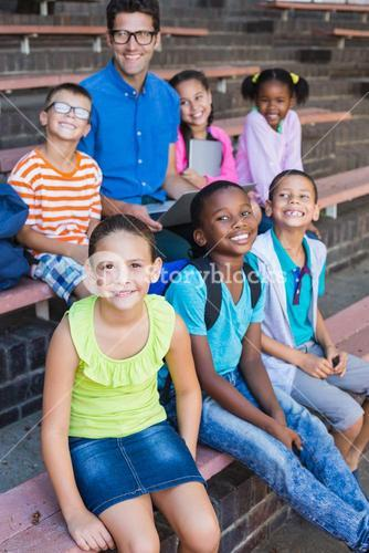 Portrait of teacher and kids sitting on bench