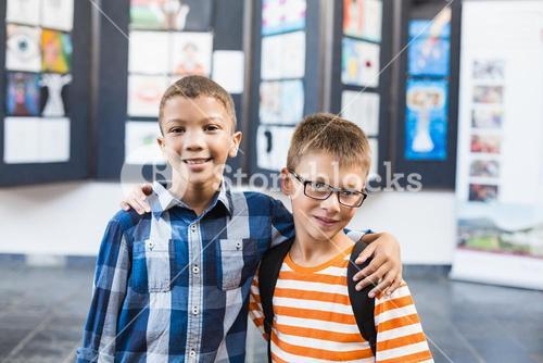 Smiling school kids standing with arm around in classroom