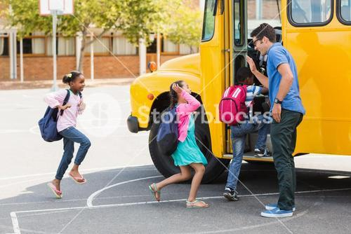 Teacher giving high five to kids while entering in bus