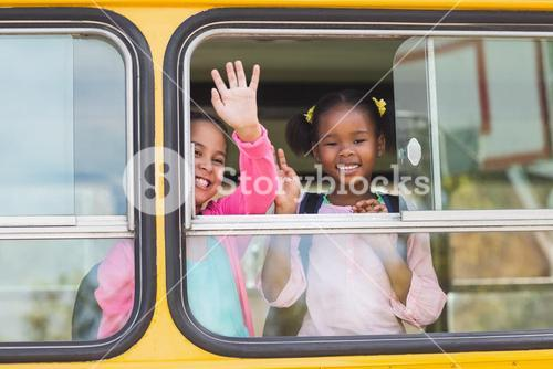 Portrait of school kids waving hand from bus