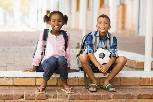 Portrait of kids sitting on stairs at school