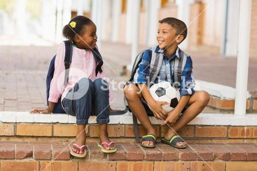 Smiling kids sitting on stairs at school