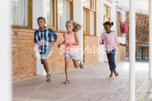 Smiling school kids running in corridor