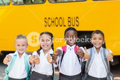 Smiling kids showing thumbs up in front of school bus