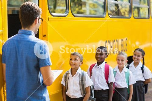 Teacher updating check list of kids