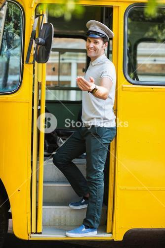 Bus driver standing at the entrance of bus and gesturing