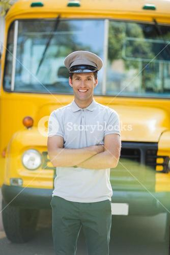 Smiling bus driver standing with arms crossed in front of bus